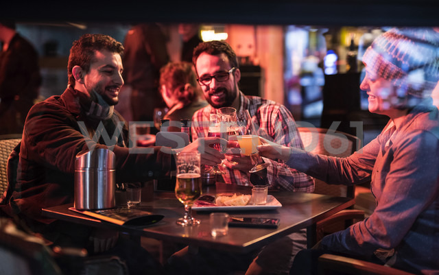 Three friends at a pub at night clinking beer glasses - JASF000369