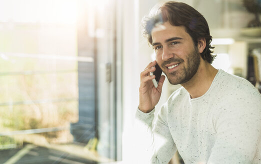 Portrait of relaxed young man looking through window while telephoning with smartphone - UUF006480
