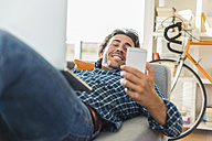 Young man lying on the couch with laptop looking at his smartphone - UUF006486