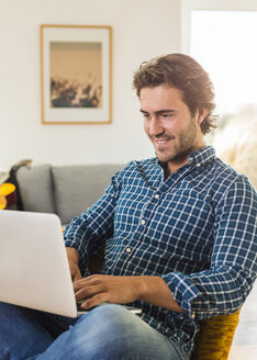 Portrait of smiling young man sitting in the living room using laptop - UUF006495