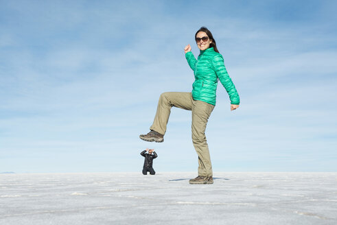 Bolivia, Salar de Uyuni, woman kicking small man, visual illusion - GEMF000711