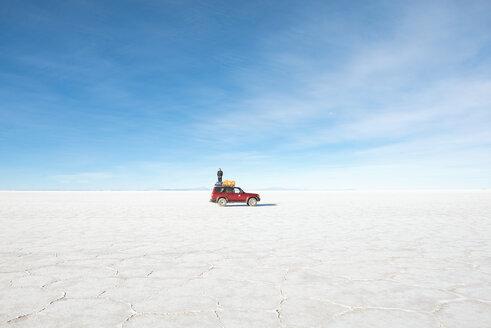 Bolivia, Atacama, Altiplano, Salar de Uyuni, Man standing on a 4x4 car - GEMF000714