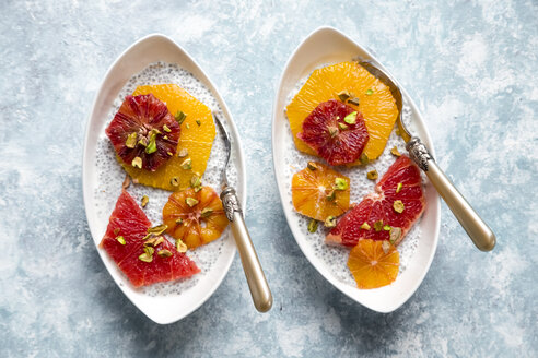 Chia Pudding and slices of orange blood orange and grapefruit, bowls on wood - SARF002539