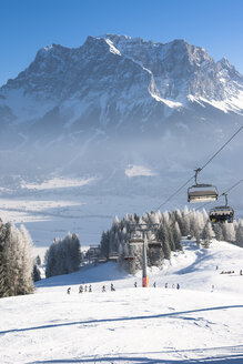 Austria, Tyrol, Lermoos, chair lift in winter landscape with view to Zugspitze - AMF004749