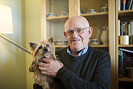 Portrait of senior man with his Yorkshire terrier at home - RAEF000859