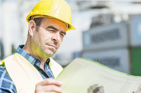 Man wearing hard hat reading document at container port - UUF006521