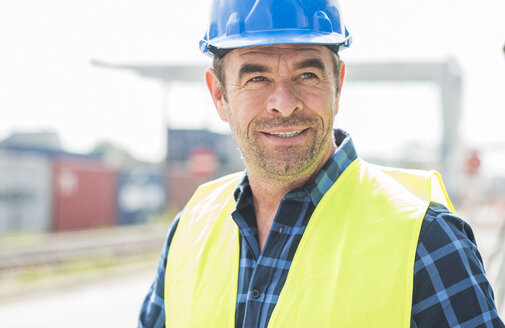 Portrait of confident man wearing hard hat at container port - UUF006524
