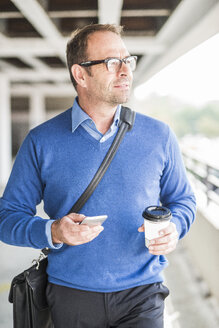 Businessman with cell phone and coffee to go on the move - UUF006533