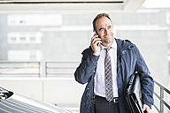 Businessman on cell phone in car park - UUF006536