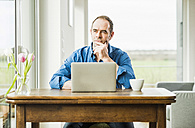 Businessman at home with laptop at wooden table thinking - UUF006539