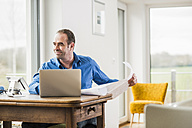Businessman at home with laptop and plan at wooden table - UUF006545