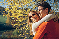 Happy couple embracing in autumn forest - CHAF001568