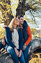 Happy couple enjoying autumn in a forest sitting on trunk - CHAF001571