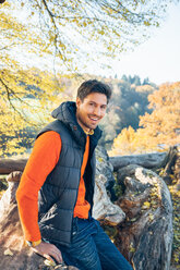 Portrait of smiling young man in a forest on trunk - CHAF001574