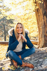 Smiling woman enjoying autumn in a forest sitting on a trunk - CHAF001580