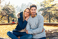 Happy couple enjoying autumn in a forest sitting on trunk - CHAF001583