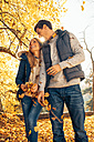 Happy couple having fun in autumn in a forest - CHAF001589