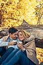 Smiling couple holding cups in autumn forest - CHAF001592