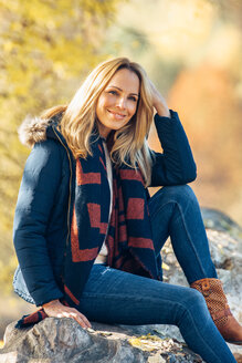 Smiling woman enjoying autumn in a forest sitting on a trunk - CHAF001607