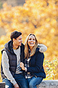 Happy couple enjoying autumn in a forest sitting on a trunk - CHAF001616