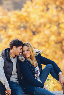 Happy couple enjoying autumn in a forest sitting on a trunk - CHAF001619