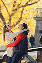 Happy couple enjoying autumn in a park - CHAF001631