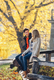 Happy couple sitting on wooden railing in autumnal park - CHAF001634