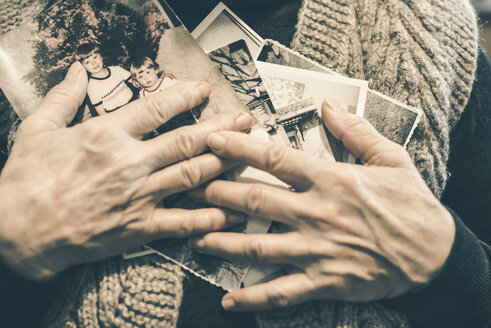 Hands of senior woman holding old photographies, close-up - DEGF000607