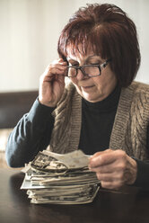 Senior woman with stack of old photographies - DEGF000610