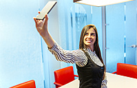 Portrait of smiling businesswoman taking selfie with smartphone in a conference room - MGOF001349