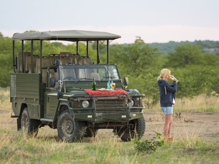 Namibia, Outjo, tourist drinking glass of champagne in Ongava Wild Reservat - AMF004760