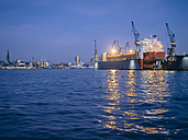 Germany, Hamburg, Harbour, Containership in a dock in the evening - KRPF001721
