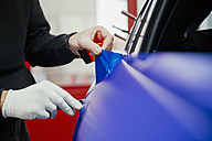 Man wrapping car with vinyl foil - ZEDF000053