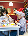 Two little girls tinkering Christmas decoration - MGOF001351