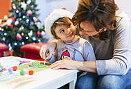 Mother helping her little daughter tinkering Christmas decoration - MGOF001360