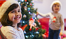 Portrait of happy girl at Christmas time with herlittle sister in the background - MGOF001366
