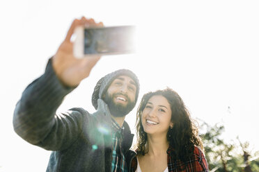 Young happy couple taking a selfie in backlight - JRFF000403