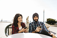 Young couple using their cell phones at a street cafe - JRFF000406