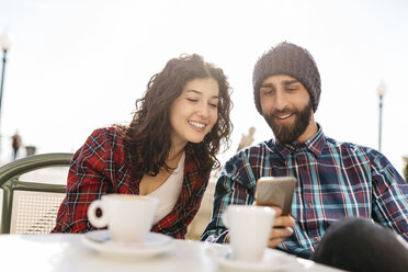 Young man showing his cell phone to girlfriend at a street cafe - JRFF000409