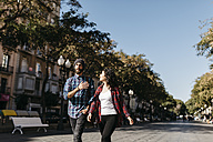 Spain, Tarragona, young couple walking in the city - JRFF000412