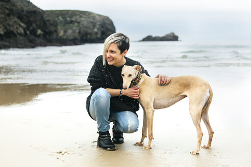 Spain, Llanes, happy young woman with her greyhound on the beach - MGOF001373