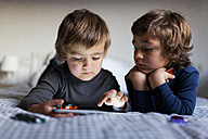 Two little boys lying on bed playing with digital tablet - VABF000138