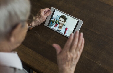Senior man using mini tablet for skyping with his grandson - UUF006570