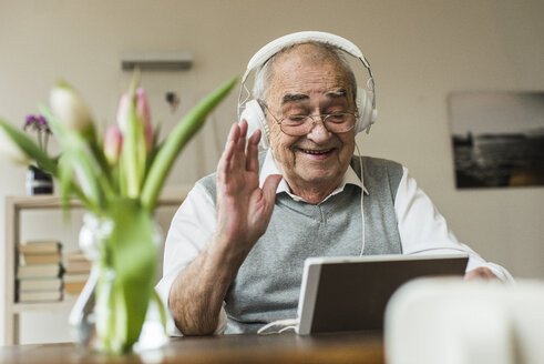 Senior man using mini tablet and headphones for skyping at home - UUF006573