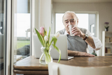 Portrait of senior man with laptop drinking glass of water at home - UUF006606