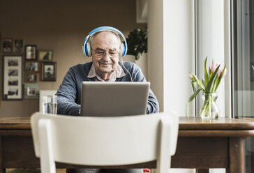 Senior man using laptop and headphones at home - UUF006609