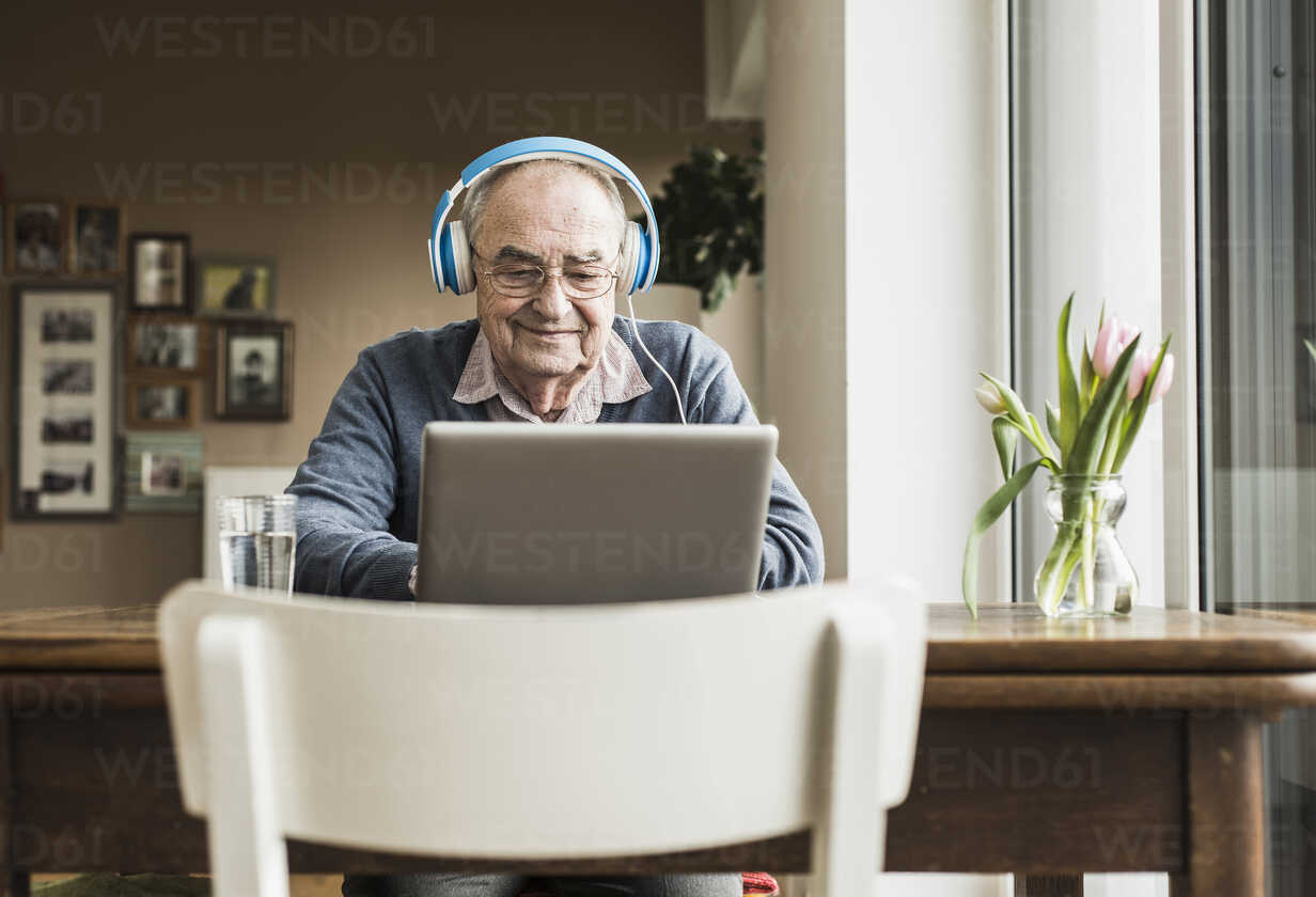 Senior man using laptop and headphones at home - UUF006609 - Uwe Umstätter/Westend61