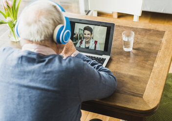 Senior man using laptop and headphones for skyping with his grandson - UUF006612
