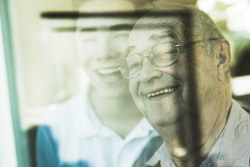 Portrait of senior man and his grandson in the background looking through window - UUF006624
