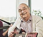 Portrait of senior man playing guitar - UUF006633